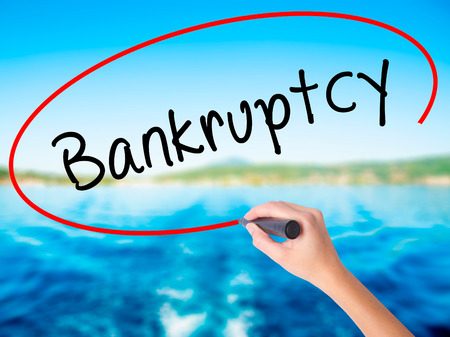 Woman Hand Writing Bankruptcy on blank transparent board with a marker isolated over water background. Business concept. Stock Photo