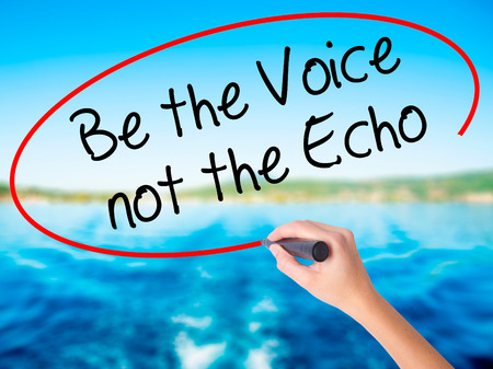 to be or not be: Woman Hand Writing Be the Voice not the Echo on blank transparent board with a marker isolated over water background. Business concept. Stock Photo Stock Photo