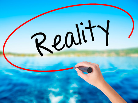 Woman Hand Writing  Reality on blank transparent board with a marker isolated over water background. Business concept. Stock Photo