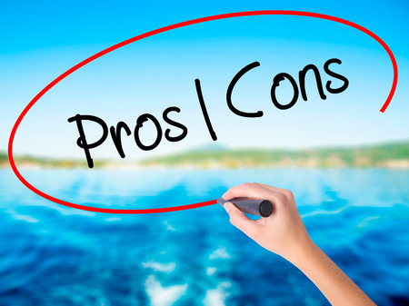 Woman Hand Writing Pros  Cons on blank transparent board with a marker isolated over water background. Business concept. Stock Photo