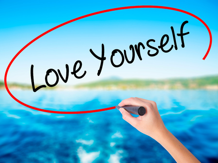 egoistic: Woman Hand Writing Love Yourself on blank transparent board with a marker isolated over water background. Business concept. Stock Photo