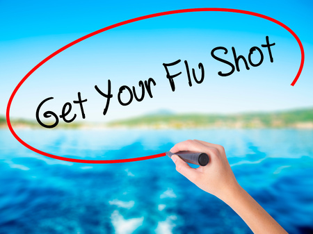 Woman Hand Writing Get Your Flu Shot on blank transparent board with a marker isolated over water background. Business concept. Stock Photo Stock Photo