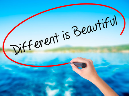 differentiation: Woman Hand Writing Different is Beautiful on blank transparent board with a marker isolated over water background. Business concept. Stock Photo