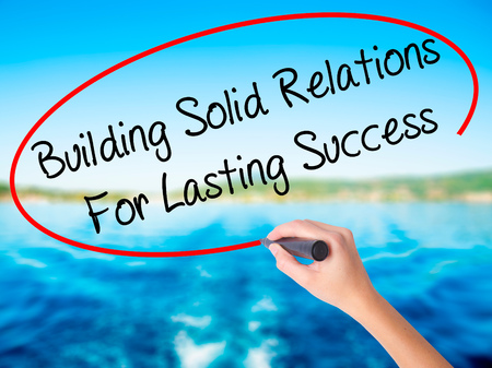 lasting: Woman Hand Writing Building Solid Relations For Lasting Success on blank transparent board with a marker isolated over water background. Business concept. Stock Photo