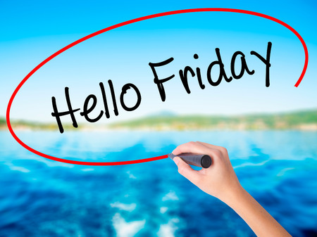 Woman Hand Writing Hello Friday on blank transparent board with a marker isolated over water background. Business concept. Stock Photo