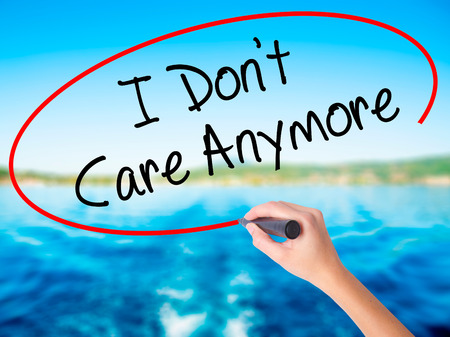 Woman Hand Writing I Dont Care Anymore on blank transparent board with a marker isolated over water background. Business concept. Stock Photo Stock Photo