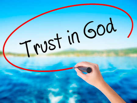 Woman Hand Writing Trust in God on blank transparent board with a marker isolated over water background. Business concept. Stock Photo Stock Photo