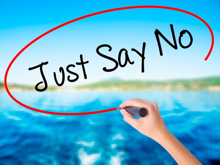 demonstrator: Woman Hand Writing Just Say No on blank transparent board with a marker isolated over water background. Business concept. Stock Photo