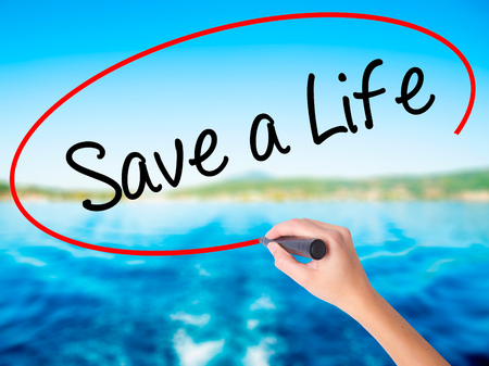 Woman Hand Writing Save a Life  on blank transparent board with a marker isolated over water background. Business concept. Stock Photo Stock Photo