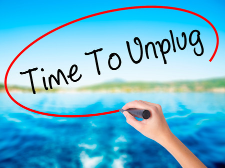 Woman Hand Writing Time To Unplug on blank transparent board with a marker isolated over water background. Business concept. Stock Photo Stock Photo
