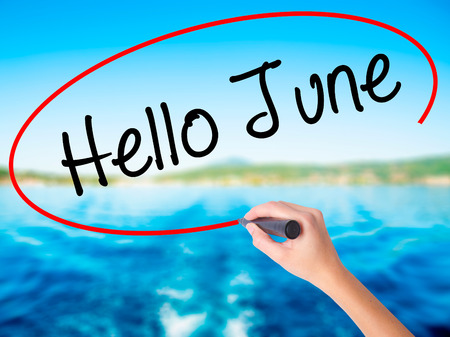 Woman Hand Writing Hello June  on blank transparent board with a marker isolated over water background. Business concept. Stock Photo Stock Photo