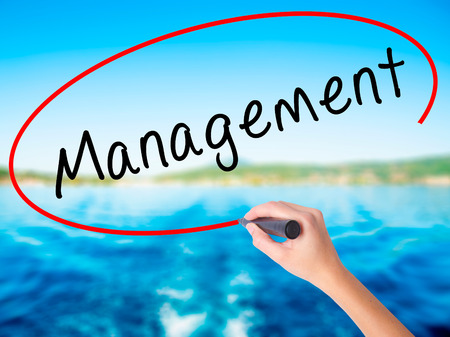execute: Woman Hand Writing Management on blank transparent board with a marker isolated over water background. Business concept. Stock Photo