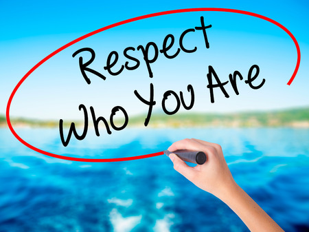 Woman Hand Writing Respect Who You Are on blank transparent board with a marker isolated over water background. Business concept. Stock Photo Stock Photo