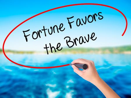 Woman Hand Writing Fortune Favors the Brave on blank transparent board with a marker isolated over water background. Business concept. Stock Photo Stock Photo