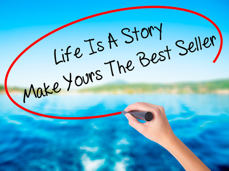 narrator: Woman Hand Writing Life Is A Story Make Yours The Best Seller on blank transparent board with a marker isolated over water background. Business concept. Stock Photo