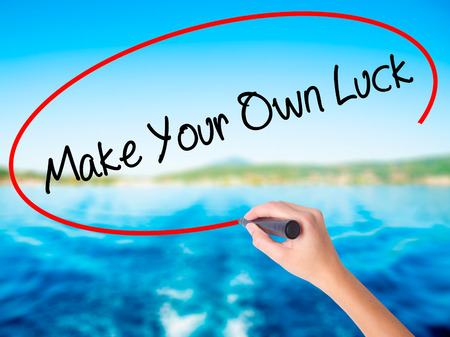 Woman Hand Writing Make Your Own Luck on blank transparent board with a marker isolated over water background. Business concept. Stock Photo