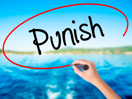 discouraging: Woman Hand Writing Punish on blank transparent board with a marker isolated over water background. Business concept. Stock Photo