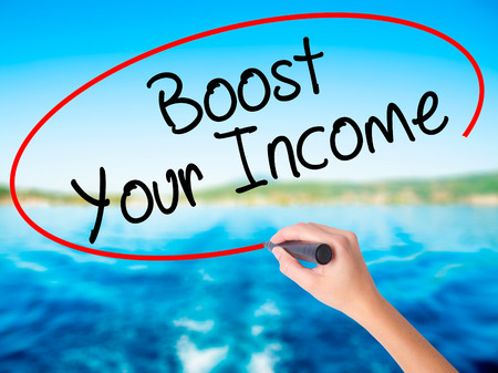 emolument: Woman Hand Writing Boost Your Income on blank transparent board with a marker isolated over water background. Business concept. Stock Photo
