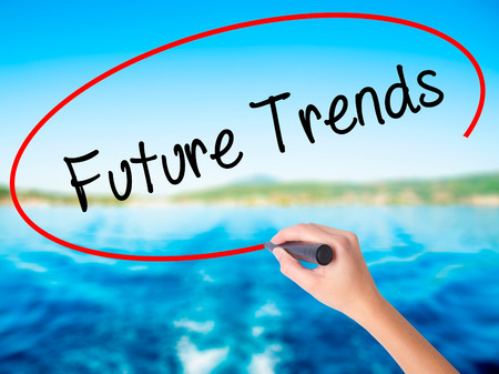Woman Hand Writing Future Trends on blank transparent board with a marker isolated over water background. Business concept. Stock Photo