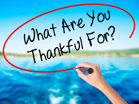 Woman Hand Writing What Are You Thankful For? on blank transparent board with a marker isolated over water background. Business concept. Stock Photo