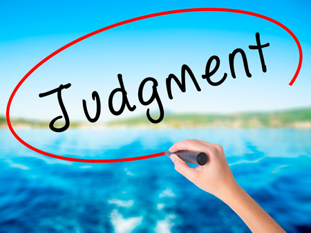 Woman Hand Writing Judgment on blank transparent board with a marker isolated over water background. Business concept. Stock Photo