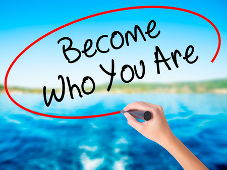 Woman Hand Writing Become Who You Are on blank transparent board with a marker isolated over water background. Business concept. Stock Photo Stock Photo