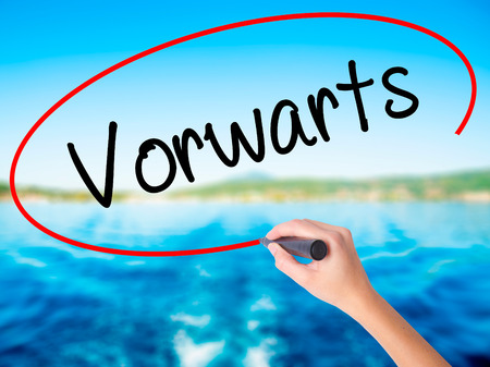 Woman Hand Writing Vorw??¤rts  (Forward In German)  on blank transparent board with a marker isolated over water background. Business concept. Stock Photo