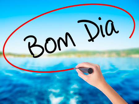 "Woman Hand Writing ""Bom Dia"" (In portuguese - Good Morning)  on blank transparent board with a marker isolated over water background. Business concept. Stock Photo Stock Photo"
