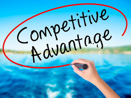 Woman Hand Writing Competitive Advantage on blank transparent board with a marker isolated over water background. Business concept. Stock Photo