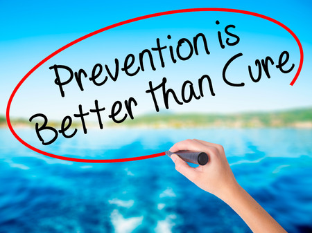 cure prevention: Woman Hand Writing Prevention is Better than Cure on blank transparent board with a marker isolated over water background. Business concept. Stock Photo