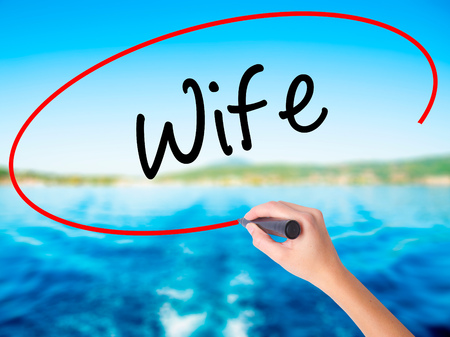 ex wife: Woman Hand Writing Wife on blank transparent board with a marker isolated over water background. Business concept. Stock Photo
