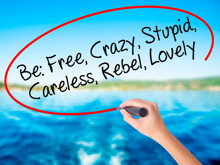 Woman Hand Writing Be: Free, Crazy, Stupid, Careless, Rebel, Lovely on blank transparent board with a marker isolated over water background. Business concept. Stock Photo Stock Photo