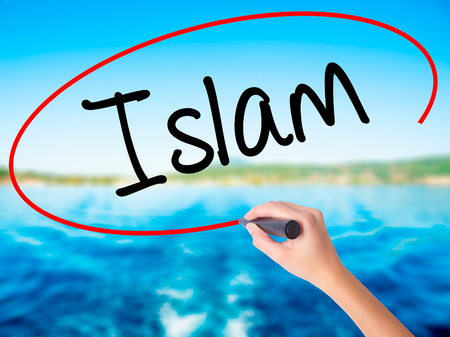 Woman Hand Writing Islam on blank transparent board with a marker isolated over water background. Business concept. Stock Photo