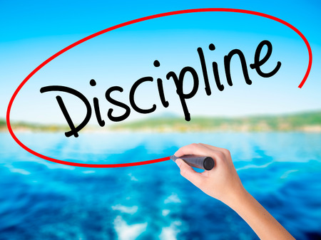 Woman Hand Writing Discipline on blank transparent board with a marker isolated over water background. Business concept. Stock Photo Stock Photo