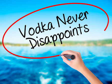 Woman Hand Writing Vodka Never Disappoints on blank transparent board with a marker isolated over water background. Business concept. Stock Photo Stock Photo