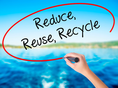 reduce reuse recycle: Woman Hand Writing Reduce Reuse Recycle on blank transparent board with a marker isolated over water background. Business concept. Stock Photo