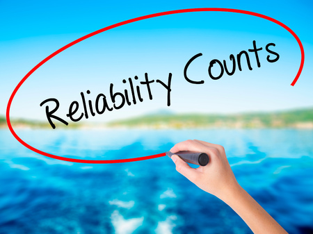 Woman Hand Writing Reliability Counts on blank transparent board with a marker isolated over water background. Business concept. Stock Photo Imagens