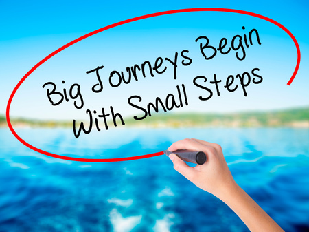 Woman Hand Writing Big Journeys Begin With Small Steps  on blank transparent board with a marker isolated over water background. Business concept. Stock Photo Stock Photo