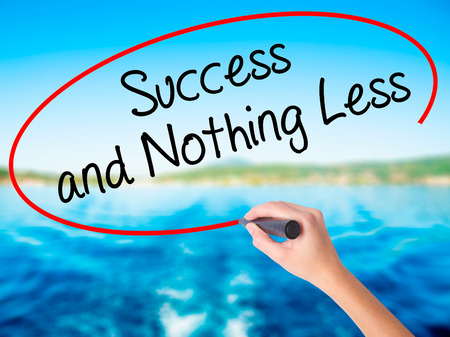 work less: Woman Hand Writing Success and Nothing Less on blank transparent board with a marker isolated over water background. Business concept. Stock Photo