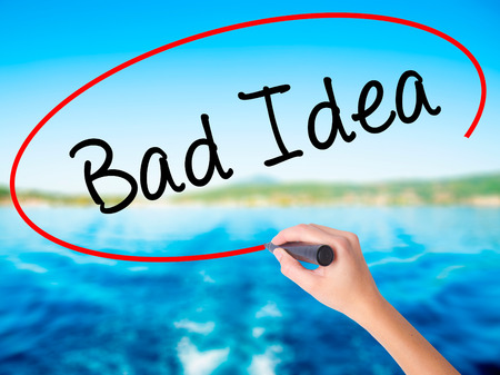 unacceptable: Woman Hand Writing Bad Idea on blank transparent board with a marker isolated over water background. Business concept. Stock Photo