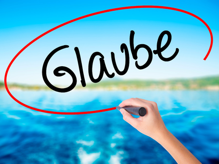 glaube: Woman Hand Writing Glaube (Believe in German) on blank transparent board with a marker isolated over water background. Business concept. Stock Photo Stock Photo