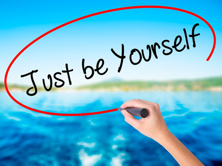 true self: Woman Hand Writing Just be Yourself on blank transparent board with a marker isolated over water background. Business concept. Stock Photo
