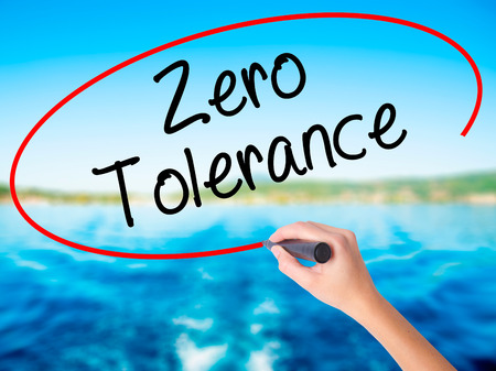 Woman Hand Writing Zero Tolerance on blank transparent board with a marker isolated over water background. Business concept. Stock Photo