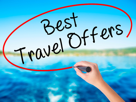 Woman Hand Writing Best Travel Offers  with a marker over transparent board. Isolated on white. Travel technology, internet concept. Stock Image Stock Photo