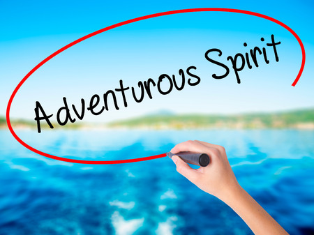 Woman Hand Writing Adventurous Spirit on blank transparent board with a marker isolated over water background. Business concept. Stock Photo