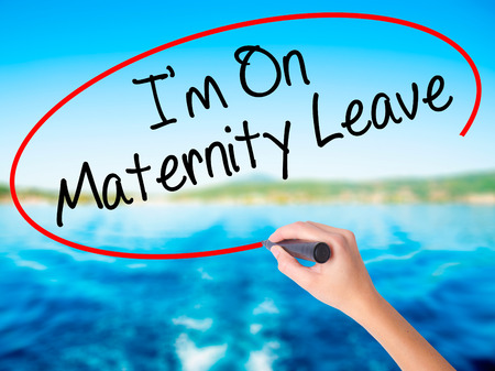 Woman Hand Writing  Im On Maternity Leave on blank transparent board with a marker isolated over water background. Business concept. Stock Photo