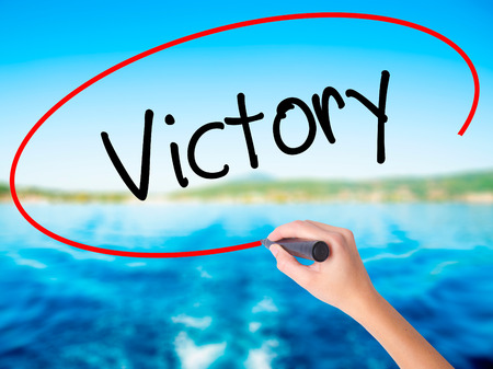 aspirational: Woman Hand Writing Victory  on blank transparent board with a marker isolated over water background. Business concept. Stock Photo