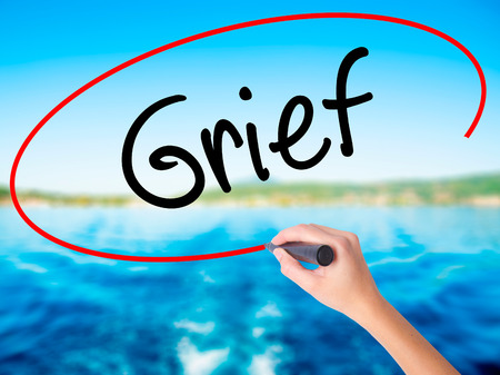 Woman Hand Writing Grief on blank transparent board with a marker isolated over water background. Business concept. Stock Photo