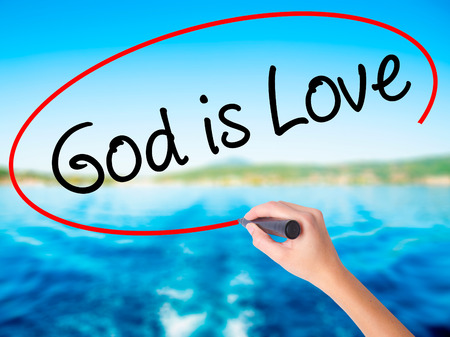 Woman Hand Writing God is Love on blank transparent board with a marker isolated over water background. Business concept. Stock Photo Stock Photo