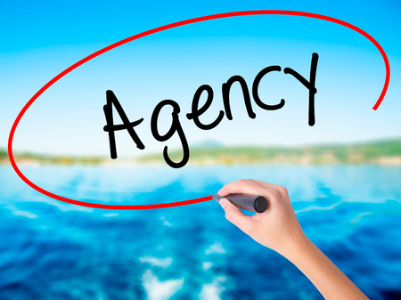Woman Hand Writing Agency on blank transparent board with a marker isolated over water background. Business concept. Stock Photo Stock Photo